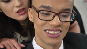 Il capo della giovane donna bisbiglia nell'orecchio del suo impiegato sorridente africano, i flirt, fps di concetto 50 di molesti video d archivio