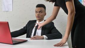 Il capo della giovane donna seduce il suo impiegato africano, le gru a benna da un legame, flirtante, fps di concetto 50 di moles stock footage