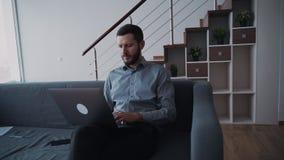 Il capo di Formalwear sta sedendosi sul sofà e sta funzionando facendo uso del computer e del telefono a casa stock footage