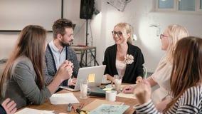 Il capo femminile ha riferito le buone notizie, ognuna è felice, alto--fiving gruppo di affari in un ufficio startup moderno fotografie stock