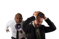 Il capo rimprovera con il megafono un impiegato disperato con un'aggressione verbale fotografia stock libera da diritti