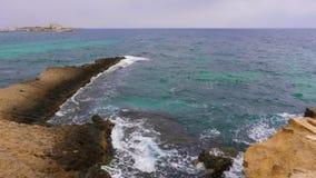 Il capo roccioso idilliaco con il blu ondeggia sulla spiaggia video d archivio
