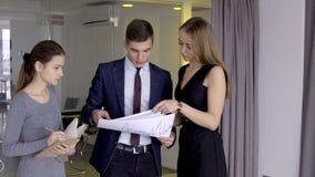 Il capo sta e controlla le carte che sono date dagli impiegati femminili in ufficio video d archivio