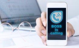 Il capo sta rivolgendo al telefono dell'impiegato di concetto fotografia stock libera da diritti