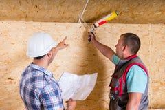 Il caporeparto Instructing Worker How da applicarsi calafata Fotografie Stock Libere da Diritti