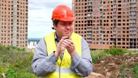 Il caporeparto, il lavoratore o l'architetto maschio del costruttore sul cantiere della costruzione è applaudenti e guardanti all video d archivio