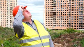 Il caporeparto, il lavoratore o l'architetto maschio del costruttore sul cantiere della costruzione guarda intorno archivi video