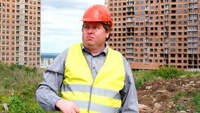 Il caporeparto, il lavoratore o l'architetto maschio del costruttore sul cantiere della costruzione imita il lavoro e dirige la c archivi video