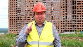 Il caporeparto, il lavoratore o l'architetto maschio del costruttore sul cantiere della costruzione non acconsente ondeggiando il archivi video