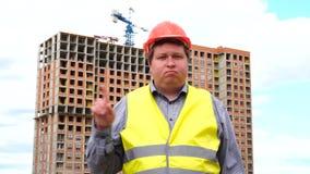 Il caporeparto, il lavoratore o l'architetto maschio del costruttore sul cantiere della costruzione non acconsente ondeggiando il video d archivio