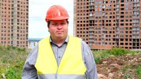 Il caporeparto, il lavoratore o l'architetto maschio del costruttore sul cantiere della costruzione sta ballando stock footage