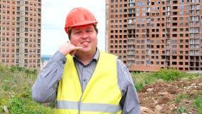 Il caporeparto, il lavoratore o l'architetto maschio del costruttore sulla rappresentazione del cantiere della costruzione mi chi stock footage