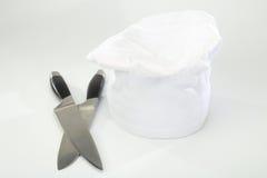 Il cappello del cuoco unico e coltelli di cottura Immagini Stock Libere da Diritti