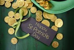 Il cappello del leprechaun del giorno della st Patricks con il cioccolato dell'oro conia Fotografie Stock