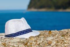 Il cappello del ` s degli uomini di colore bianco si trova sulle pietre contro lo sfondo del mare e delle montagne immagine stock