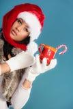 Il cappello dell'assistente di Santa della ragazza dell'inverno tiene la tazza rossa Fotografia Stock