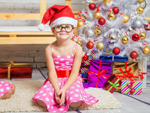 Il cappello della ragazza in rosso ed i vetri rotondi divertenti si siede sulla stuoia agli alberi di Natale Fotografie Stock