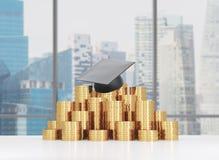 Il cappello di graduazione sta mettendo sulla piramide delle monete Un concetto di un prezzo elevato per l'istruzione dell'univer Fotografia Stock Libera da Diritti