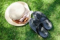 Il cappello e le scarpe mettono sull'erba Immagini Stock Libere da Diritti