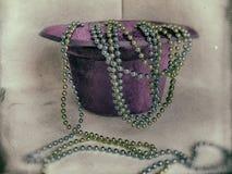 Il cappello, livello ha invertito il cilindro e le perle decorative su un fondo bianco Fotografia Stock