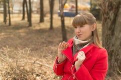 Il cappotto della ragazza in rosso su una passeggiata nel parco Immagine Stock