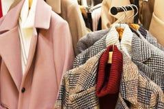 Il cappotto delle donne su un gancio in un negozio di vestiti fotografia stock