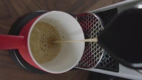 Il cappuccino è versato nella tazza rossa disposta sul vassoio di macchina automatica del caffè video d archivio