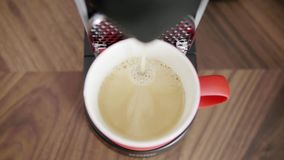 Il cappuccino è versato nella tazza rossa disposta sul vassoio di macchina automatica del caffè archivi video