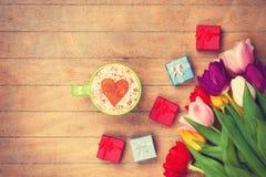 Il cappuccino ed i regali si avvicinano ai fiori Fotografie Stock Libere da Diritti