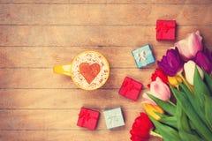 Il cappuccino ed i regali si avvicinano ai fiori Immagine Stock