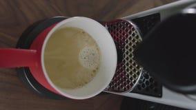 Il cappuccino sta gocciolando nella tazza rossa disposta sul vassoio di macchina automatica del caffè stock footage