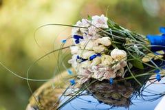 Il cappuccio di un'automobile nera è decorato con un mazzo dei fiori in uno stile di nozze Immagine Stock Libera da Diritti