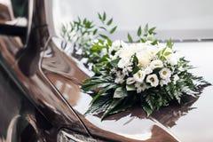 Il cappuccio di un'automobile nera è decorato con un mazzo dei fiori in uno stile di nozze Immagine Stock