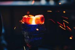 Il carbone caldo sulla ciotola di narghilé è riscaldato con le scintille rosse di un volo per la festa e fumare Fotografie Stock