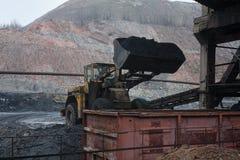 Il caricatore carica il carbone nel vagonetto fotografie stock libere da diritti