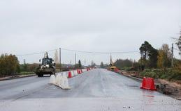 il caricatore del camion sta guidando sulla nuova strada asfaltata riparata con le recinzioni di plastica fotografia stock