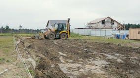 Il caricatore dell'escavatore a cucchiaia rovescia fa il lavoro al cantiere stock footage