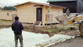 Il caricatore dell'escavatore a cucchiaia rovescia scarica le macerie ad un cantiere stock footage