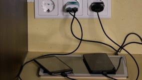 Il carico degli Smart Phone e della compressa si è collegato ai caricatori della presa a muro stock footage