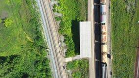 Il carico prepara il primo piano Vista aerea dei treni merci variopinti sulla stazione ferroviaria Vagoni con le merci sulla ferr video d archivio