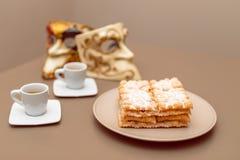 Il carnevale italiano tipico frittella Chiacchiere di Carnevale spolverato con in polvere Composizione con due tazze di caffè ed  fotografia stock