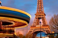 Il carosello d'annata illuminato gira davanti ad Eiffel Towe Fotografia Stock