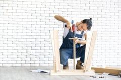 Il carpentiere asiatico dai capelli lunghi stava montando deliberatamente un wo fotografia stock libera da diritti
