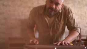 Il carpentiere bello lavora con legno stock footage