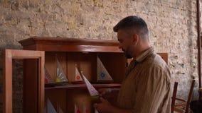 Il carpentiere bello tiene un modello di una barca di legno archivi video
