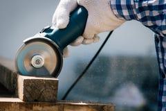 Il carpentiere che per mezzo degli strumenti ha visto il legno elettrico di taglio Fotografie Stock