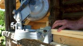 Il carpentiere che taglia la plancia di legno con la lama circolare ha visto stock footage