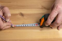 Il carpentiere con una matita segna lo spazio in bianco per mobilia fatta di legno fotografia stock libera da diritti