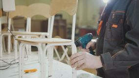 Il carpentiere del lavoratore sta avvitando la sedia per choldren su una fabbrica della mobilia Fotografia Stock Libera da Diritti