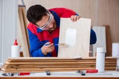 Il carpentiere del riparatore del yooung che lavora con la pittura della pittura Fotografia Stock